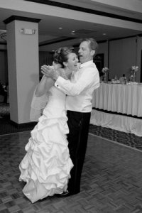 father and bride step on toes and laugh.jpg