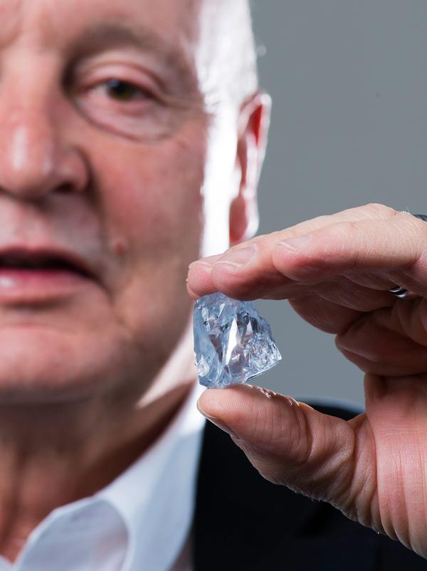 Petra Diamonds CEO Johan Dippenaar holds a 122.52-carat rare blue diamond