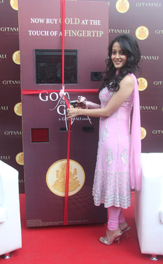 Bollywood star Raima Sen stands in front of Gitanjali Group's new ATM machine