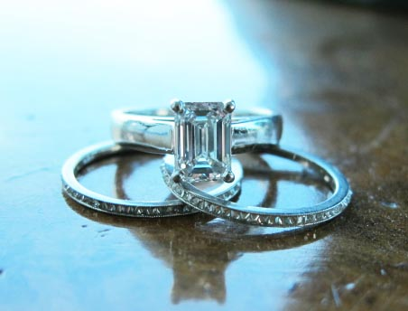 Emerald cut solitaire engagement ring with diamond wedding bands