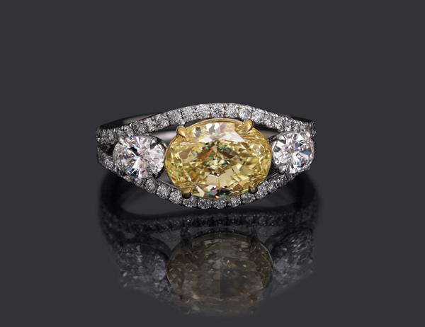 Custom oval-cut yellow diamond three-stone ring by Leon Megé