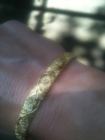 Wrist shot of Van Craeynest gold bangle bracelet