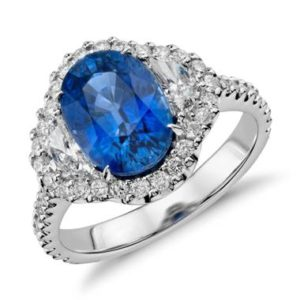 Blue sapphire and diamond halo three-stone ring set in 18K white gold at Blue Nile