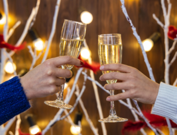 A man and woman celebrating the festive season with a glass of bubbly in either hand. Photo by Artem Kniaz on Unsplash.