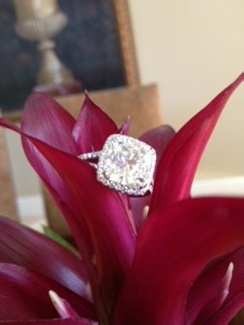 GIA certified 4.50 carat cushion cut diamond engagement ring placed on leaf.