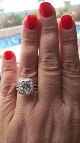 GIA certified 4.50 carat cushion cut diamond engagement ring on ring finger.