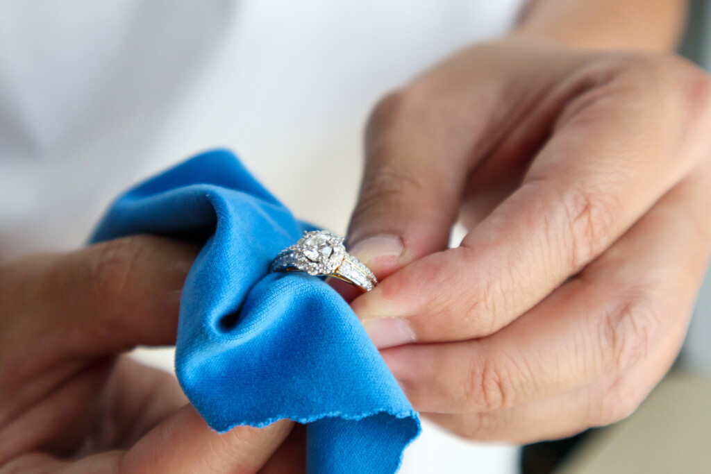 Jeweler hand polishing and cleaning jewelry diamond ring with micro fiber fabric.