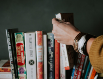 Hand reaching for books Photo by Christin Hume on Unsplash.