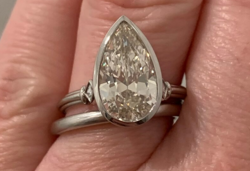 2.6+ carat pear shaped diamond ring. Its set in platinum with tri-wire and two French cut side stones.
