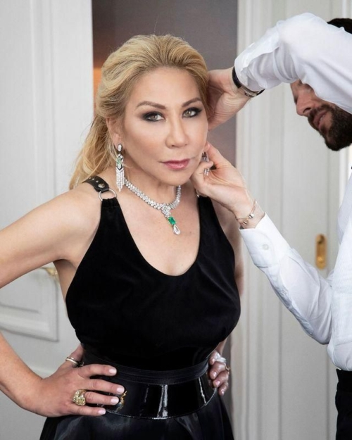 Anna shay being dressed for a photoshoot, hands on hips, blond hair, black dress, diamond and emerald necklace