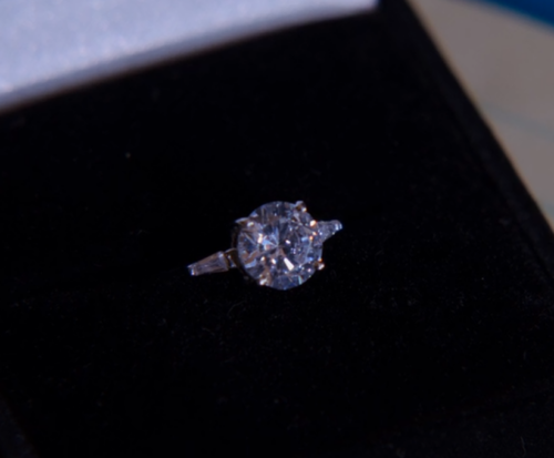 a diamond engagement ring in a black ring box