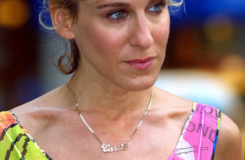 Carrie Bradshaw in her Carrie signature gold necklace