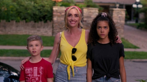 A smiling blond woman in a yellow sleeveless blouse with Ray-bans hanging from the front, on her right her brooding 15 year old biracial daughter in dark colors, on the left her 9 year old blond son in a red tee shirt. They are all taking in the view of their new house (not in image) with varying reactions.
