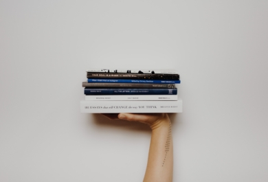 Person holding stack of books - Photo by Thought Catalog on Unsplash