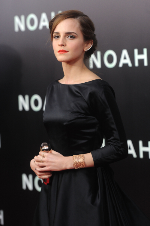 Emma Watson in a black dress with her hair up, golden lacey cuff on her wrist