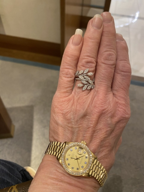 A hand with a stunning vine inspired Tiffany ring and a gold watch at the wrist