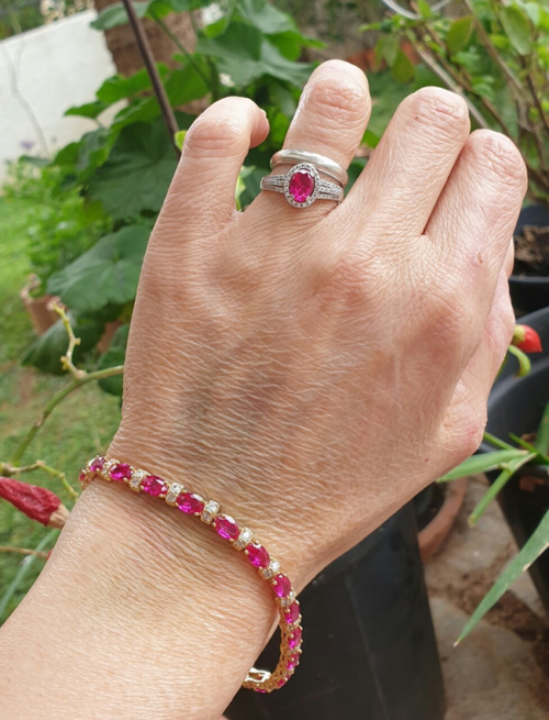 a hand with a ruby and diamond tennis bracelet and a diamond and ruby ring