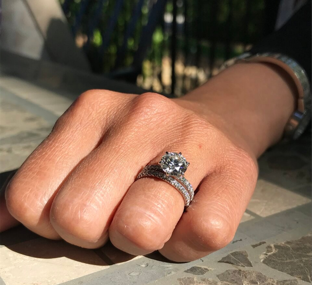 a hand with a beautiful diamond engagement ring