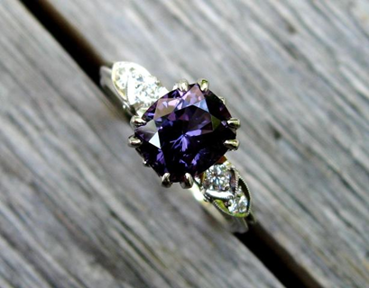 purple ring with white side diamonds in a wooden deck seam