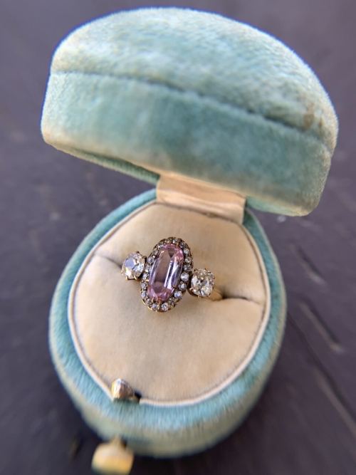 Elongated oval pink topaz with OMC side stones and an old swiss cut 20 stone halo ring in a teal velvet ring box.