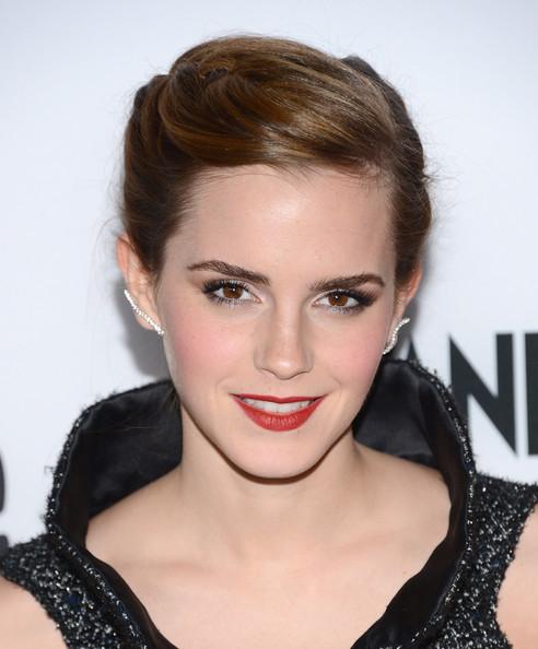 Emma Watson head and shoulders, hair in chignon, red lip, high color black top, Graziela Wave ear cuffs.