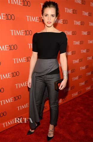 Red background, Emma Watson in a black off the shoulder shirt, grey pants and a large silver cuff bracelet at the Time 100 Gala 2015.