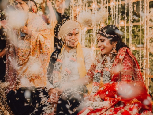 Photo from Indain Wedding couple featured in The Big Day on Netflix. They are smiling and it appears that they are in a confetti shower.