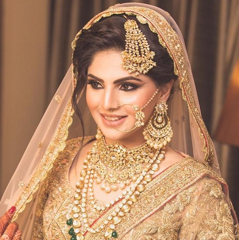 Bride in golden veil with gold jewelry, smiling. Maang Tikka Passa, Nosering, earrings, stacked necklaces