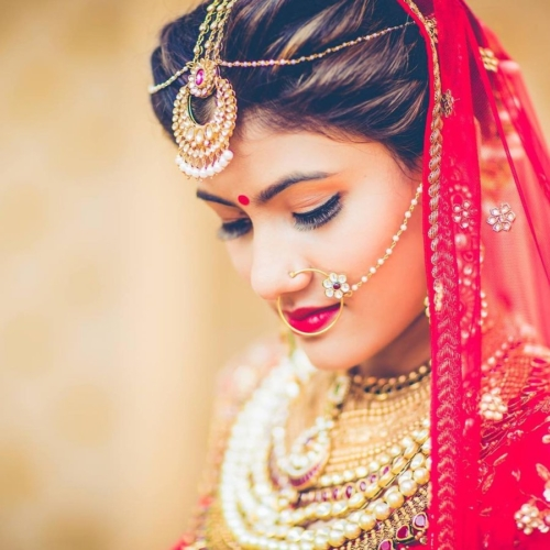 Indian bride with maang tikka, nosering, several necklaces, with a red veil