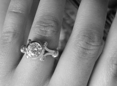 black and white image with a hand that has a diamond engagement ring on it in an ornate setting