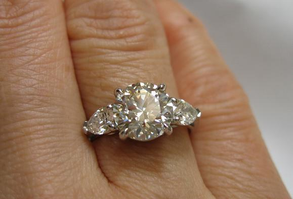 diamond engagement ring large center stone with 2 side stones, on a finger