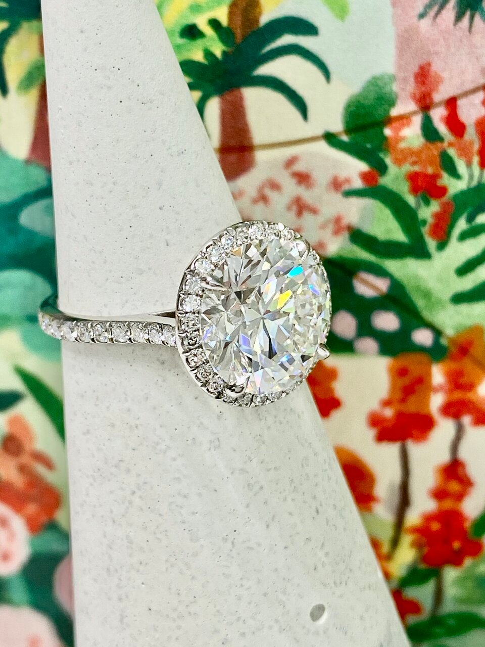 On a ring stand with a brightly floral backdrop, a custom cut 5ct Whiteflash ACA diamond ring is displayed.