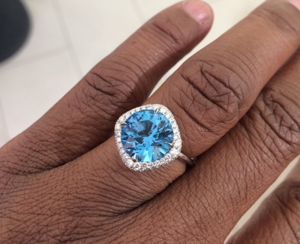 A cobblestone walkway under a hand aimed down with a stunning blue stone in white diamond prongs and halo.