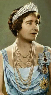 colorized image of Queen Elizabeth (The Queen Mother) as a young Queen in strands of pearls, a blue gown with her medals and pins, and the Queen Mary Fringe Tiara on her short brunette hair.