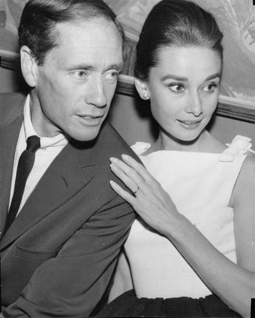 Audrey Hepburn and Mel Ferrer, image is greyscale, he is on the left in a suit and is slightly balding. Audrey is on the right, he hair is in an updo, she is wearing a white sleeveless top, her hand is on his shoulder and her wedding band is visible.