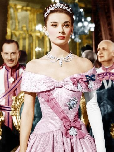Audrey Hepburn in a ballroom, from the film Roman Holiday. She is in a pink off the shoulder gown with a darker pink sash, a tiara, diamond necklace, and multiple diamond brooches. She has one full length white opera glove.