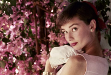 The background is pink flowers, Audrey is in a pink dress with white gloves.