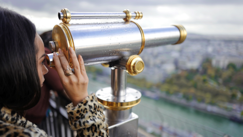 Young woman of indeterminate race in leopard print looks into a telescope that is faced at a city in the distance. She is wearing rings that are visible.