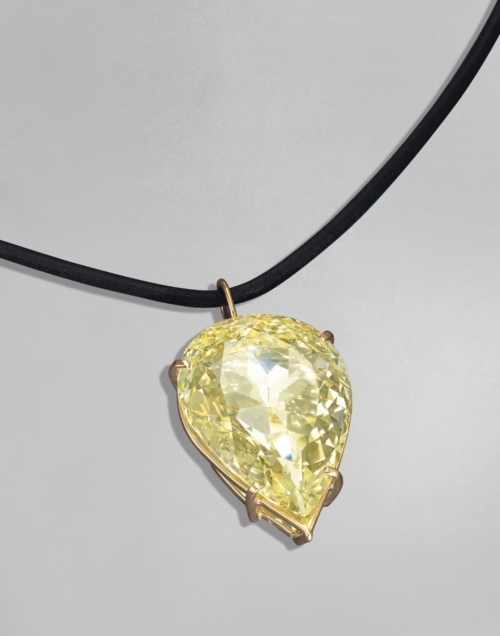 The Moon of Baroda: The 24.04ct fancy yellow, VS2 Pear on a black leather cord.