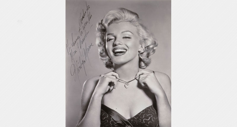 """Marilyn Monroe in grey scale, wearing the Moon of Baroda and lifting it to show it. Her autograph is to the left of her head, along with """"To Meyer Thanks for the chance to wear the Moon of Baroda."""" in her handwriting."""