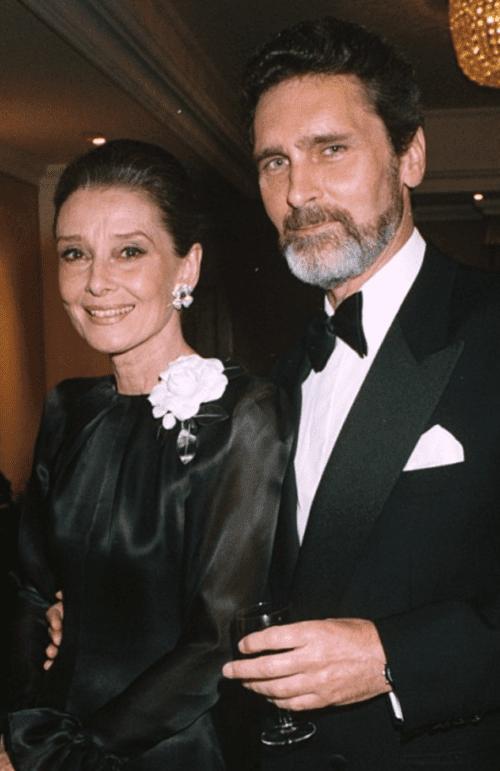 Robert Wolders and Audrey Hepburn both dressed in black tie on a black background.