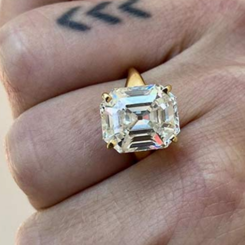 large elongated asscher diamond on a yellow gold band on a hand. One finger has a tattoo of 3 chevrons.