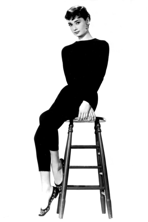 Picture of a woman in all black, black hair in chignon, cigarette pants, sitting on a stool. Wearing ballet flats. Audrey Hepburn