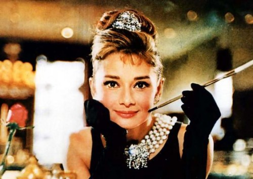 The classic image from Breakfast at Tiffany's. Store faded behind her while she has an updo, a tiara, a black dress, a large pearl and diamond necklace, black opera gloves. She had her face leaned into her hand and she is smoking a cigarette with a long cigarette holder.