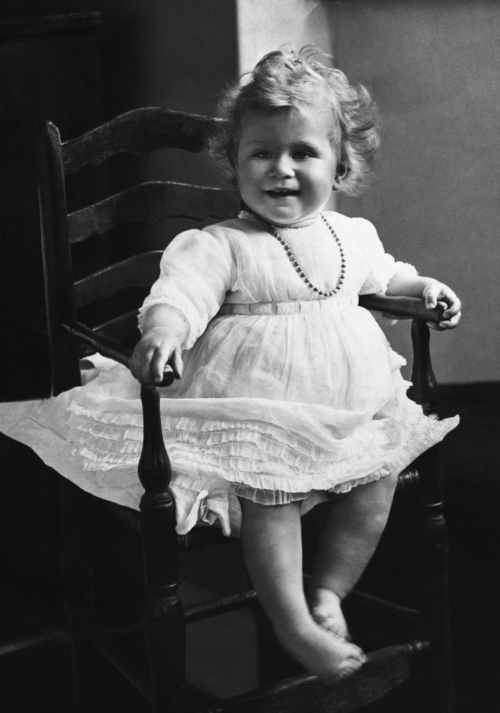 greyscale image of 1 year old Queen Elizabeth II in a chair and a white dress with a necklace. She has blonde curls