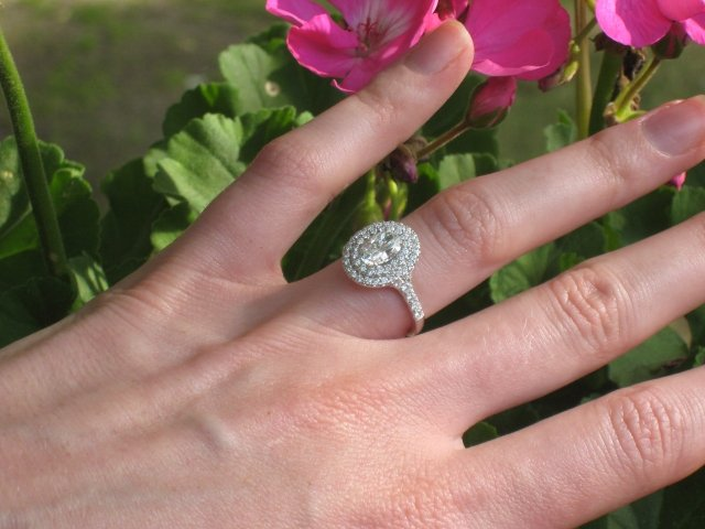 A long fingered hand with a double haloed oval diamond ring.
