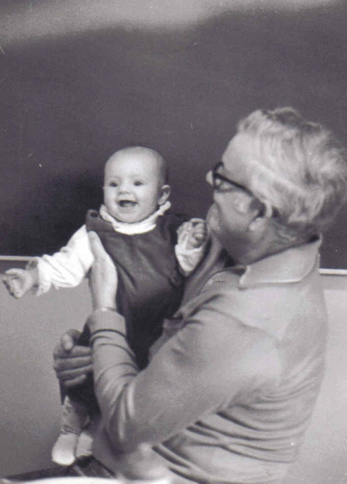 greyscale image of elderly man in glasses holding a baby in a jumper