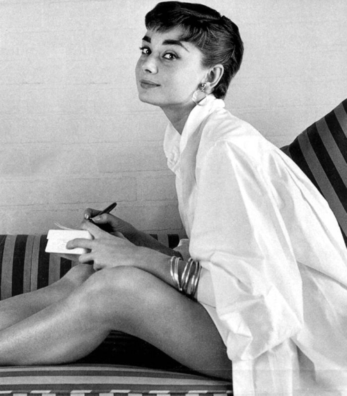 Audrey Hepburn sitting sideways on a striped sofa, image is greyscale, bare legged, pearl earrings, oversized white button down shirt, she is writing a note and has her head turned to the camera with a bit of a side eyed mischievous look.