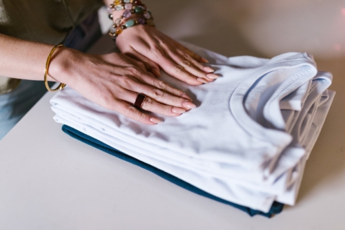 a stack of folded shirts on a white table, hands on top of them wearing rings and jewelry