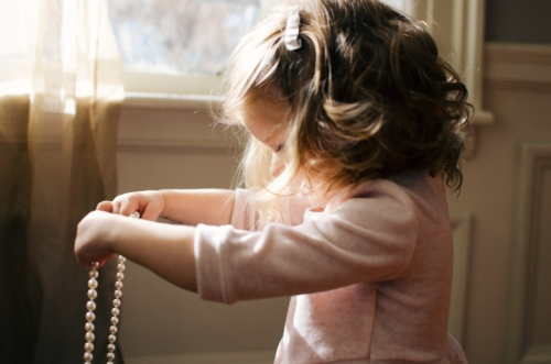 little girl with a hair clip in her curls. She is in profile in a pink shirt and holding out a string of pearls that she is looking down at. There is a curtained window behind her.